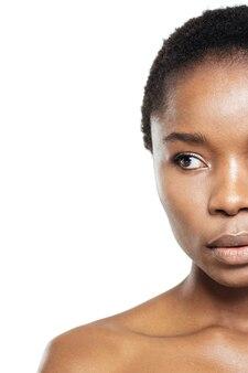 Przycięty obraz afro amerykańskiej kobiety odwracającej wzrok na białym tle