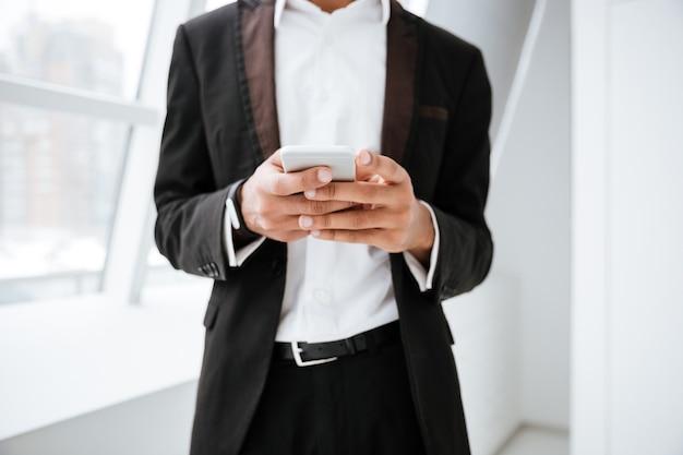 Przycięty obraz afrykańskiego biznesmena piszącego wiadomość na telefonie i stojącego w pobliżu okna w biurze