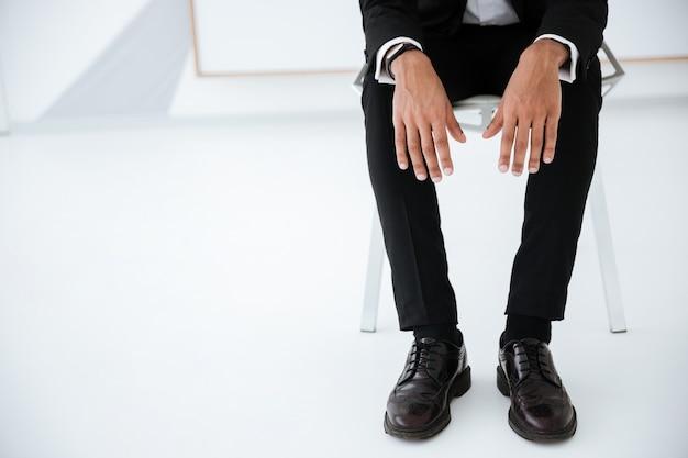 Przycięty obraz afrykańskiego biznesmena w czarnym garniturze siedzącego na krześle w biurze