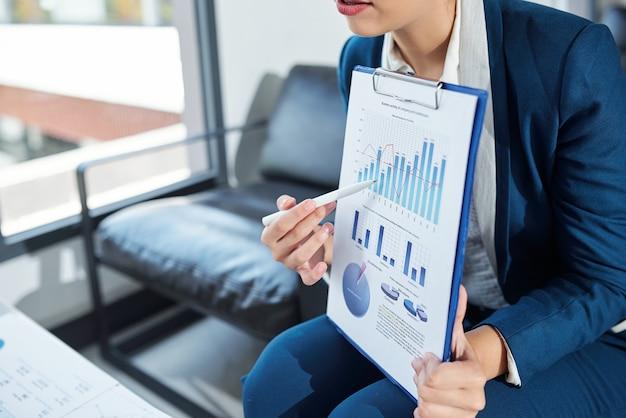 Przycięty obraz bizneswoman wskazując na wykresie słupkowym w raporcie finansowym podczas rozmowy na spotkaniu