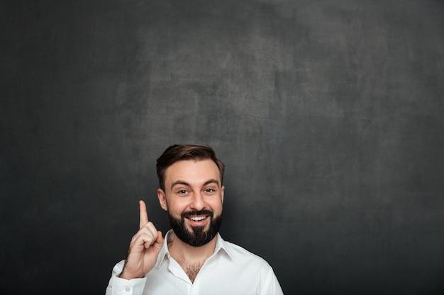 Przycięty obraz brunetka biznesmen pozowanie na kamery z pokazując palcem wskazującym w górę, czyli mieć pomysł lub po prostu pamiętać o ciemnoszarym
