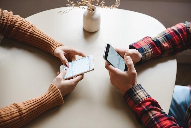 Przycięty obraz cute młoda para miłości siedzi w kawiarni w pomieszczeniu przy użyciu telefonów komórkowych.