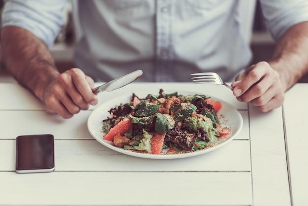 Przycięty obraz człowieka jedzenie sałatka w kawiarni.