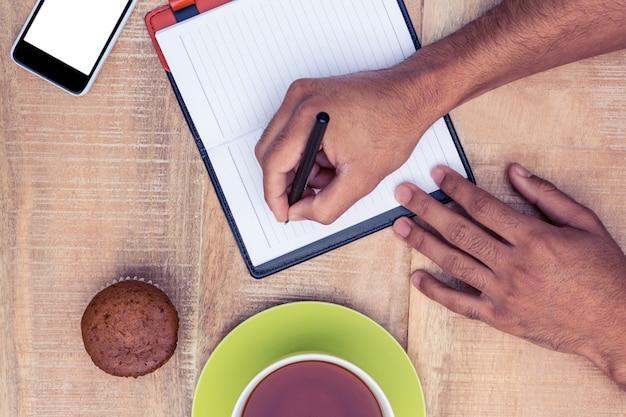 Przycięty obraz człowieka pisania na pamiętnik przy stole przez ciasto kawy i filiżanki