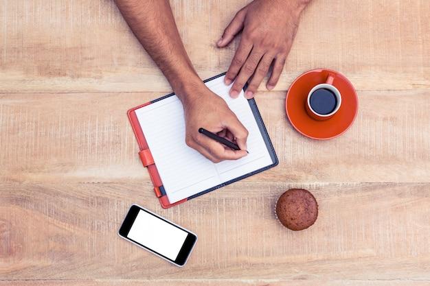 Przycięty obraz człowieka pisania na pamiętnik przy stole