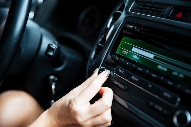 Przycięty obraz dłoni kobiety obracającej przycisk radia w samochodzie