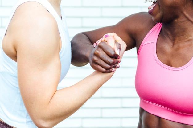 Przycięty obraz dwóch kobiet trzymających się za ręce. ręka po lewej pochodzi od białej młodej kobiety. ten po prawej pochodzi od czarnej młodej kobiety.