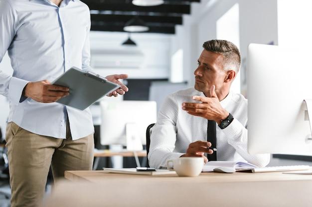 Przycięty obraz dwóch współpracowników pracujących razem z dokumentami