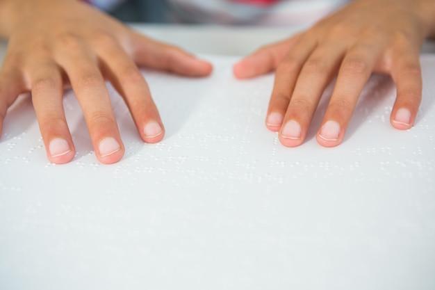 Przycięty obraz dziecka czytającego książkę braille'a