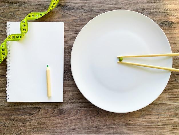 Przycięty obraz grochu na białym talerzu, z widelcem i pomiaru