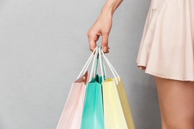 Przycięty obraz kaukaski kobieta ubrana w spódnicę trzymając kolorowe papierowe torby na zakupy z zakupami, odizolowane na szarym tle