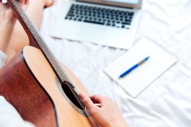 Przycięty obraz kobiecej ręki grającej na gitarze