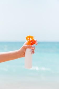 Przycięty obraz kobiecej ręki trzymającej spray ochrony przeciwsłonecznej na tle morza.