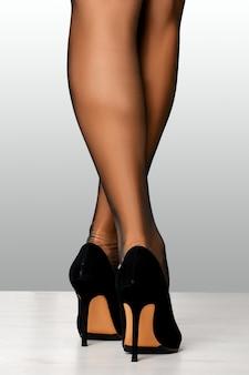 Przycięty obraz kobiecych nóg w staromodnych pończochach i wysokich obcasach