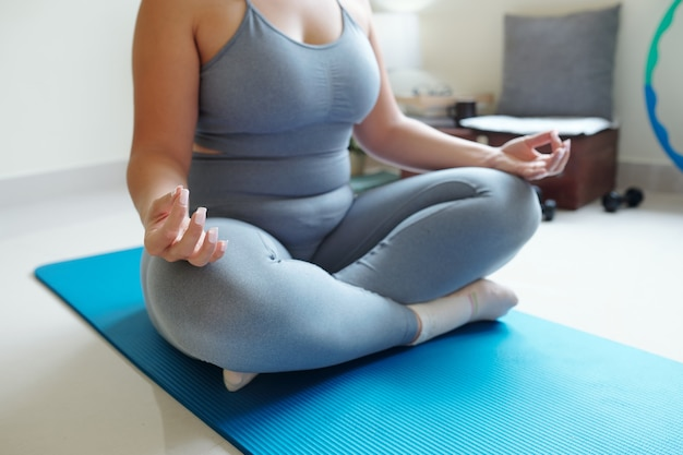 Przycięty obraz kobiety plus size siedzącej w pozycji lotosu na macie do jogi, koncepcji uważności i duchowości