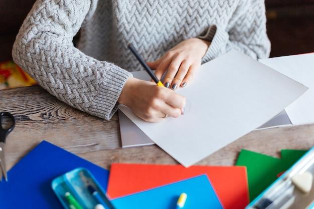 Przycięty obraz kobiety rysującej na papierze