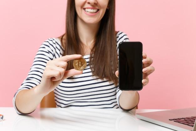 Przycięty obraz kobiety trzymającej metalową monetę bitcoin w złotym kolorze przyszłej waluty telefon komórkowy z pustym pustym ekranem siedzi przy biurku