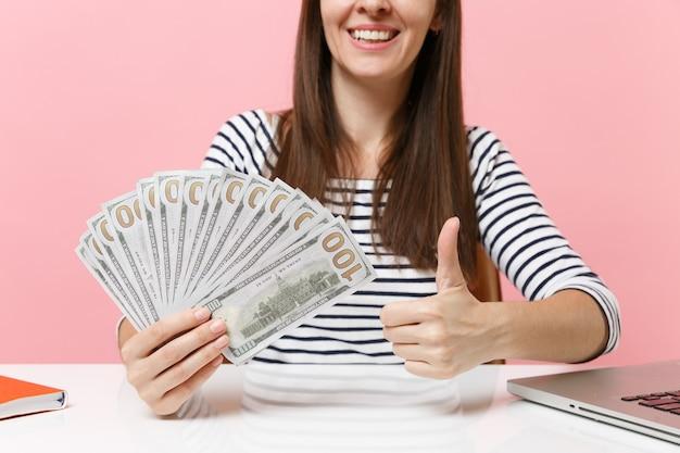 Przycięty obraz kobiety trzymającej pakiet dużo pieniędzy w gotówce pokazujący kciuk do góry i siedzący przy biurku