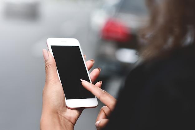 Przycięty obraz kobiety trzymającej się za ręce trzymający smartfon z pustą kopią ekranu dla wiadomości tekstowych