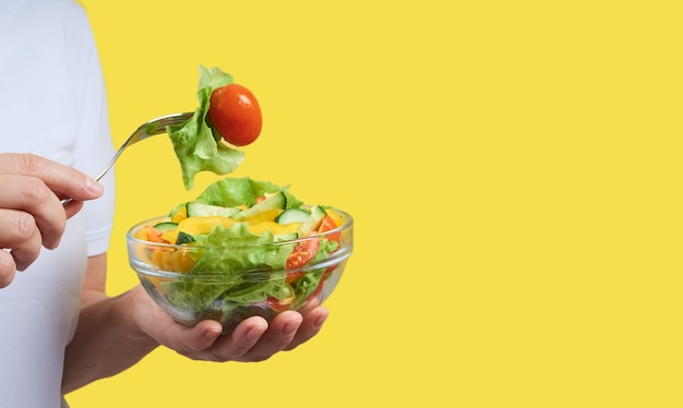 Przycięty obraz kobiety trzymającej talerz sałatki warzywnej