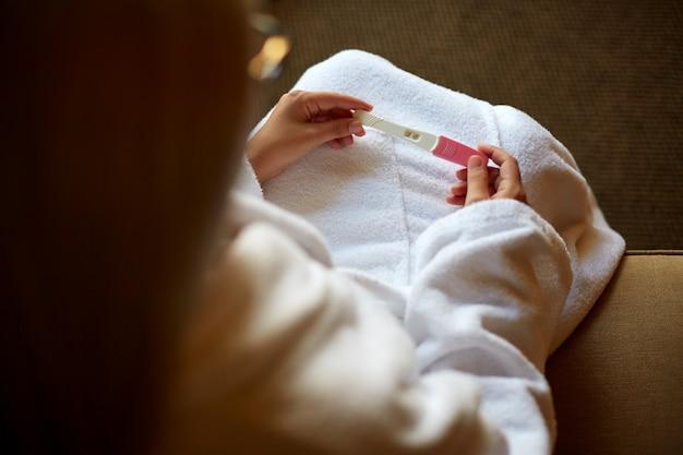 Przycięty obraz kobiety trzymającej test ciążowy na kolanach