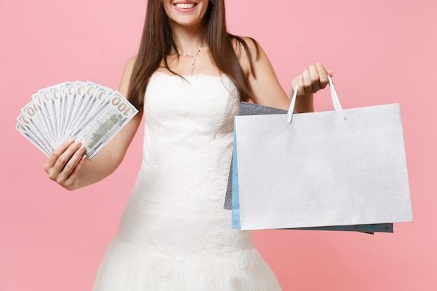 Przycięty obraz kobiety w białej sukni trzymającej pakiet dużo pieniędzy w gotówce, wielokolorowe paczki torby z zakupami po zakupach