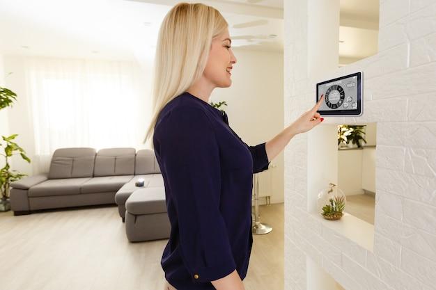 Przycięty obraz kobiety wprowadzającej tajny kod klucza w celu uzyskania dostępu i przejścia do budynku za pomocą aplikacji na telefonie komórkowym, kobieta naciskająca przyciski na panelu sterowania w celu rozbrajania systemu inteligentnego domu