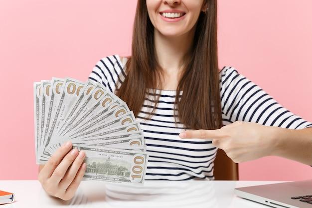 Przycięty obraz kobiety wskazującej palcem wskazującym na wiązce wiele dolarów w gotówce i siedzącej przy biurku