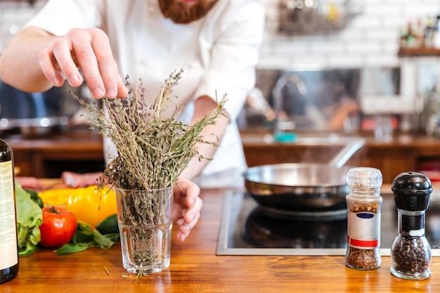 Przycięty obraz kucharza przygotowującego jedzenie w kuchni