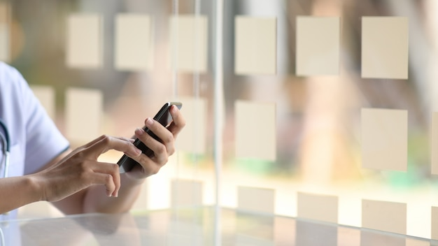 Przycięty obraz lekarza za pomocą telefonu komórkowego w ręce w biurze
