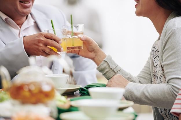 Przycięty obraz małżeństwa starszej pary opiekającej szklanki soku lub koktajlu owocowego, gdy siedzi przy stole jadalnym