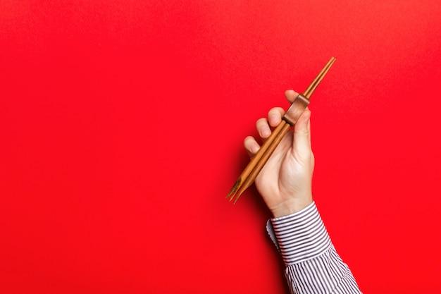 Przycięty obraz męskiej ręki trzymającej pałeczki