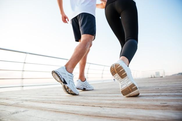 Przycięty obraz mężczyzny i kobiety biegających na świeżym powietrzu przy molo