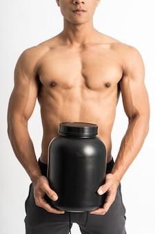 Przycięty obraz mężczyzny z umięśnionym ciałem niosącym czarną butelkę z dwiema rękami stojącymi do przodu