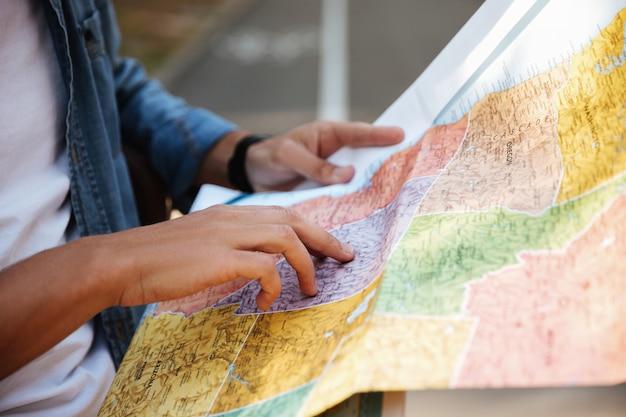Przycięty obraz młodego człowieka, patrząc na mapę