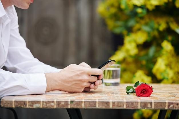 Przycięty obraz młodego mężczyzny siedzącego w kawiarni na świeżym powietrzu i wysyłającego sms-a do przyjaciela podczas oczekiwania na randkę