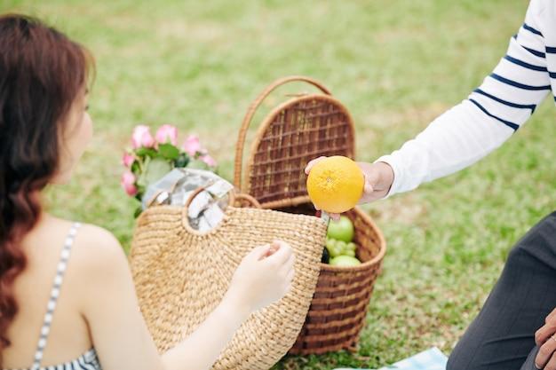 Przycięty obraz młodego mężczyzny wyciągającego pomarańczę z kosza piknikowego dla swojej dziewczyny