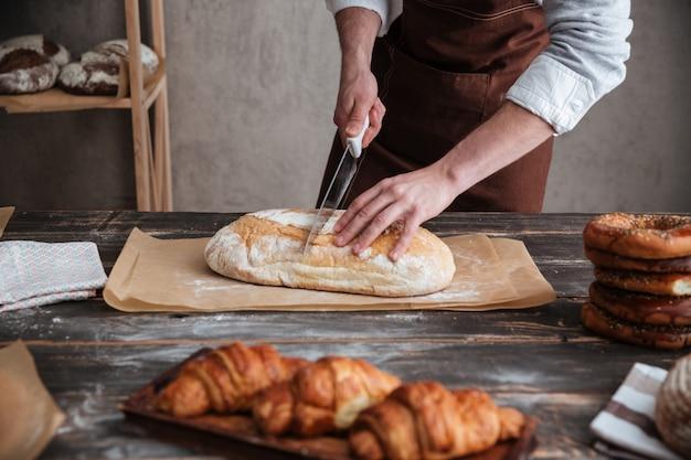 Przycięty obraz młodego piekarza pokroić chleb.
