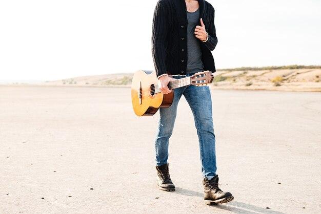 Przycięty obraz młodego przypadkowego mężczyzny chodzącego z gitarą nad morzem