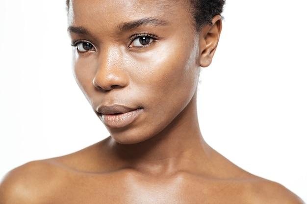 Przycięty obraz młodej afroamerykańskiej kobiety patrzącej na kamerę na białym tle