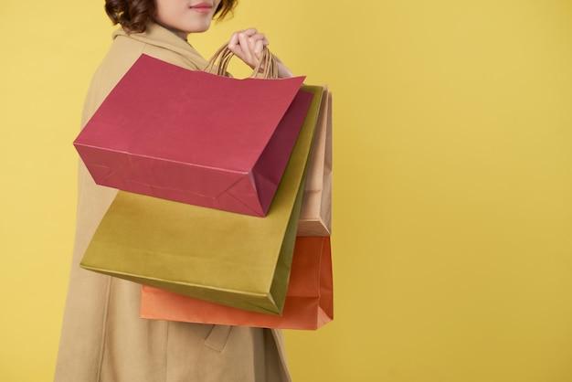 Przycięty obraz młodej kobiety trzymającej wiele toreb na zakupy i odwracającej się z powrotem do aparatu, odizolowanej na żółto
