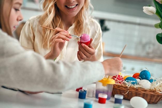 Przycięty obraz młodej kobiety z małą dziewczynką cute przygotowują się do obchodów wielkanocy. szczęśliwa rodzina w uszach króliczka spędza razem czas przed wielkanocą podczas malowania jajek.