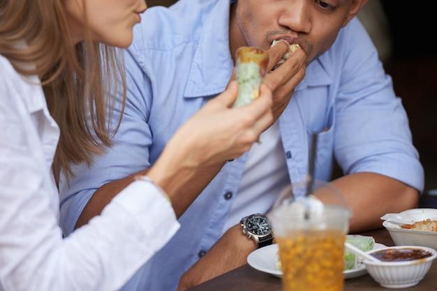 Przycięty obraz młodej pary jedzącej pyszne sajgonki
