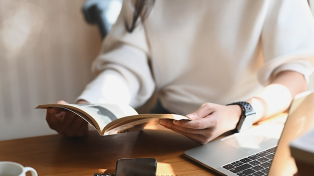 Przycięty obraz młodej pięknej kobiety trzymającej / czytającej książki w dłoniach przed laptopem komputerowym, filiżanką kawy i smartfonem przy nowoczesnym drewnianym stole z wygodnym salonem jako
