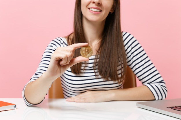 Przycięty obraz młodej uśmiechniętej kobiety trzymającej bitcoina, metalową monetę w złotym kolorze, przyszła waluta siedząca przy białym biurku