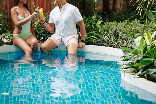 Przycięty obraz pary siedzącej przy hotelowym basenie wśród bujnych roślin i pijącej pyszne koktajle owocowe