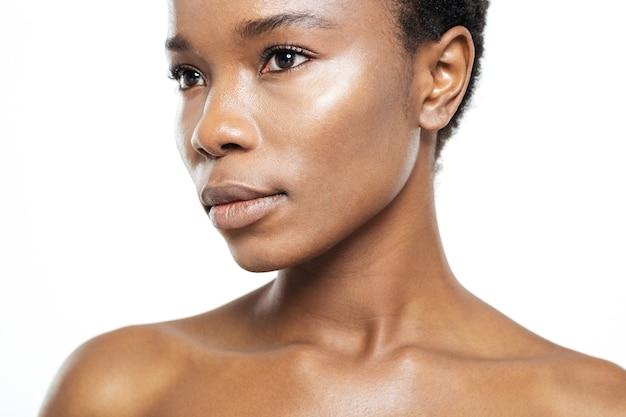 Przycięty obraz pięknej afroamerykańskiej kobiety odwracającej wzrok na białym tle