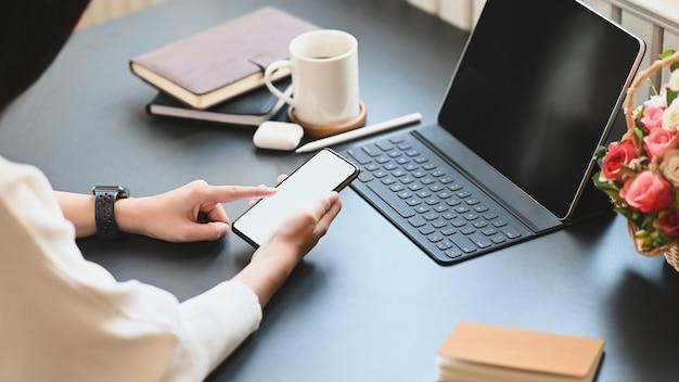 Przycięty obraz pięknej kobiety pracującej jako sekretarka trzyma / używa białego pustego ekranu smartfona, siedząc przed swoim tabletem komputerowym ze skrzynką na klawiaturę nad biurem