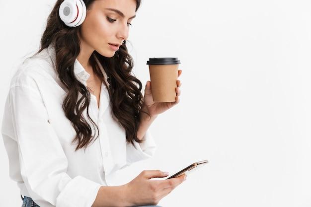 Przycięty obraz pięknej młodej kobiety z długimi kręconymi włosami brunetki, ubrana w białą koszulę, siedząca na białym tle nad białą ścianą, ciesząca się słuchaniem muzyki przez słuchawki podczas korzystania z telefonu komórkowego