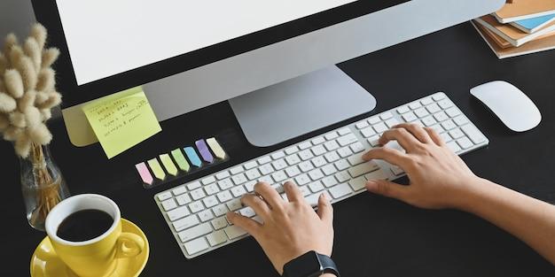Przycięty obraz pisania na klawiaturze bezprzewodowej, który nakłada na czarne biurko z monitorem komputera, myszą, stosem książek, filiżanką kawy, dziką trawą w wazonie i umieszcza.